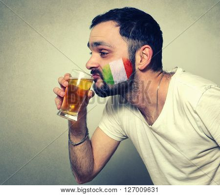 funny bearded sport fan of Italy drinking beer