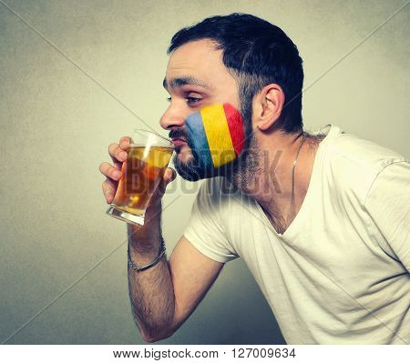 funny bearded sport fan of Romania drinking beer
