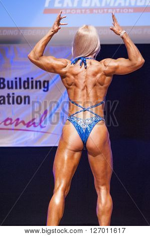 MAASTRICHT THE NETHERLANDS - OCTOBER 25 2015: Female fitness model Kinga Golebiewska flexes her muscles and shows her best physique in a back double biceps pose on stage at the World Grandprix Bodybuilding and Fitness of the WBBF-WFF