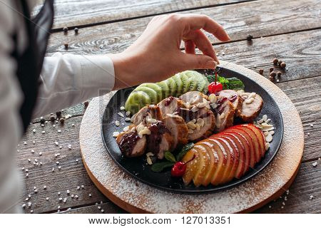 Chief decorated  baked veal on wooden table. Chief decorated  dietary meat with fresh tropical fruits. Top view on food stylist at work. POV on food decoration.
