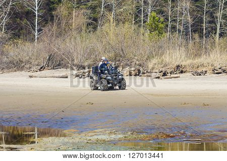 Russia Siberia Novosibirsk region Ob river - April 24 2016: the family of three rides a Quad bike