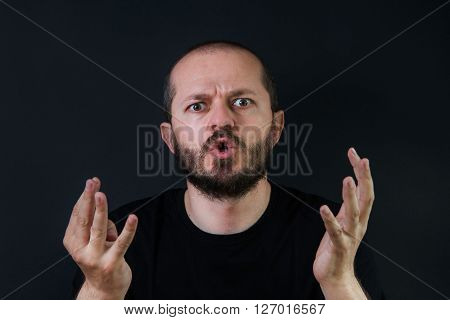 Violent, aggressive man with beard and mustaches on black background in low key, yelling and threatening
