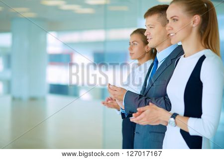 Smiling business people applauding a good presentation in the office