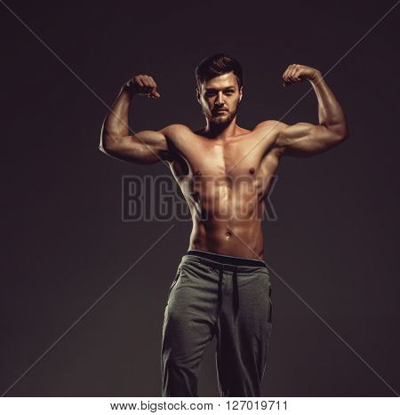 Athletic Handsome Man Showing Biceps Muscles, Studio Shot