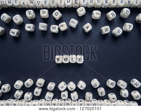 Word Sold Of Small White Cubes Next To A Bunch Of Other Letters On The Surface Of The Composition On
