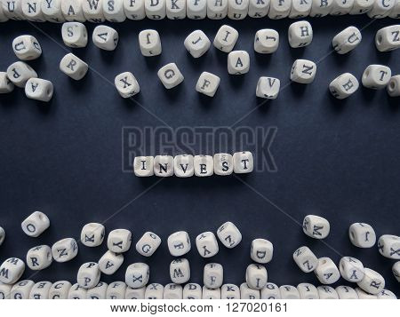 Word Invest Of Small White Cubes Next To A Bunch Of Other Letters On The Surface Of The Composition