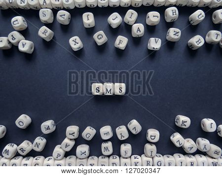 Word Sms Of Small White Cubes Next To A Bunch Of Other Letters On The Surface Of The Composition On