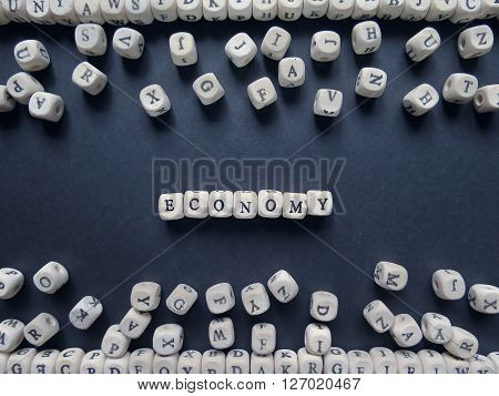 Word Economy Of Small White Cubes Next To A Bunch Of Other Letters On The Surface Of The Composition