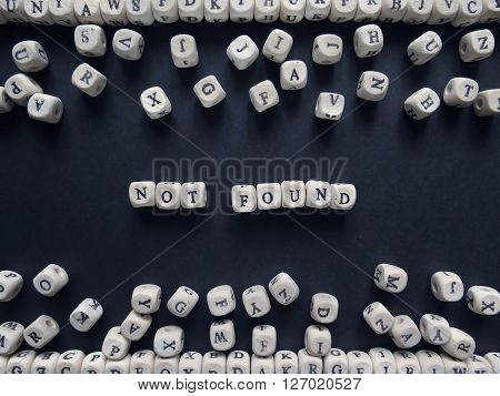 Word Not Found Of Small White Cubes Next To A Bunch Of Other Letters On The Surface Of The Compositi