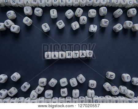 Word Hashtag Of Small White Cubes Next To A Bunch Of Other Letters On The Surface Of The Composition