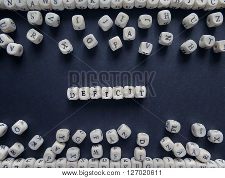 Word Deficit Of Small White Cubes Next To A Bunch Of Other Letters On The Surface Of The Composition