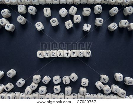 Word Strategy Of Small White Cubes Next To A Bunch Of Other Letters On The Surface Of The Compositio