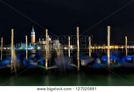 Gondolas anchored on Grand Canal in Venice - long exposure night shot with motion blurred gondolas