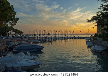 Sunset and parked boats at the harbour of small italian city Sirmione on Garda lake