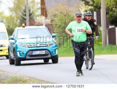 PILSEN CZECH REPUBLIC - APRIL 23, 2016: Jaroslav Kovar last hero of Plzensky pulmaraton (half marathon) run. Running in cold rainy weather. Most popular international sport event in Western Bohemia.