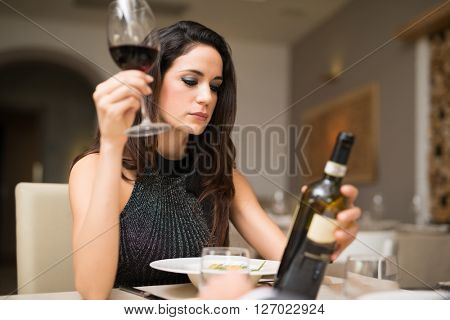 Portrait of a woman enjoying a glass of red wine in a restaurant
