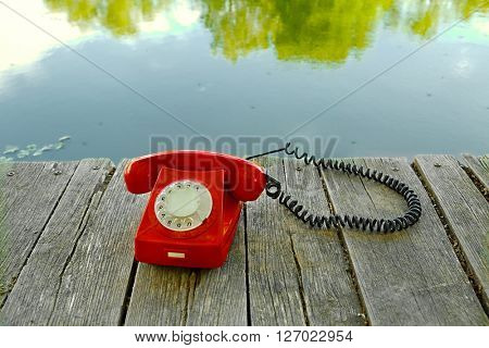 Old telephone on a lakeside pier