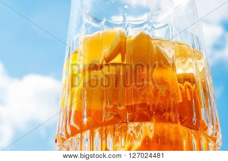 Home made orange tangerine and lemon lemonade or sangria over blue sky background