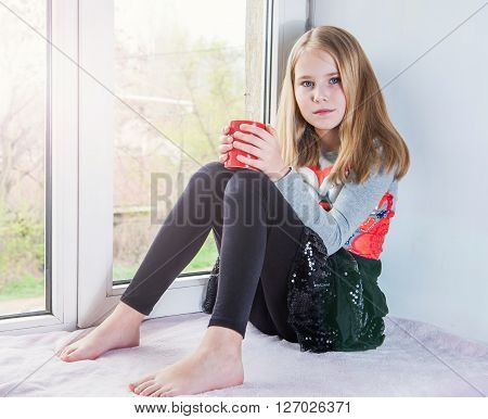 Little beauty girl sitting with cup at the window