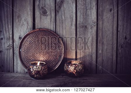 Burning candles and a copper tray on an old wooden board background, vintage decor