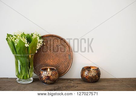 Simple home decoration, lilies of the valley in a vase and candles on the shelf by the white wall background