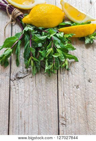Lemon and mint on wooden table. Ingredients for lemonade and cocktails. Copy space