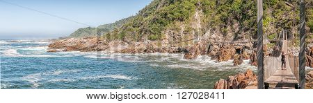 STORMS RIVER MOUTH SOUTH AFRICA - FEBRUARY 29 2016: Unidentified tourists on the suspension bridge over the mouth of the Storms River. The restaurant is visible to the far left