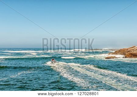 STORMS RIVER MOUTH SOUTH AFRICA - FEBRUARY 29 2016: Unidentified tourists on an inflatable speedboat exiting the mouth of the Storms River