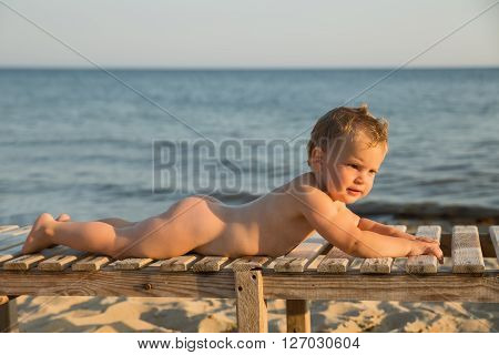 Cute babe sunbathing on the beach lying on a wooden lounger