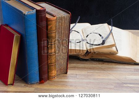 Books and glasses on wooden table desktop