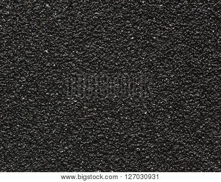 Black sandpaper texture macro shot background (closeup)