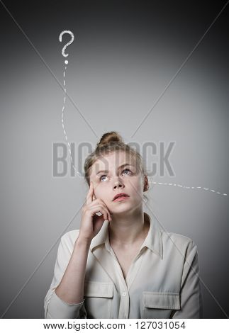 Girl in white full of doubts and hesitation. Girl and question mark above her head. Young slim woman.