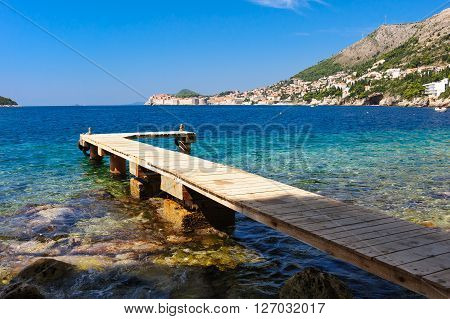 Wooden pier on the beach below St. Jacob's church and Belvedere hotel across from Dubrovnik