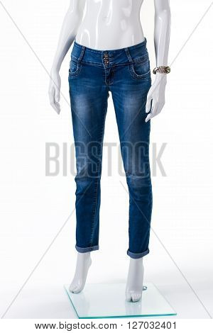 Lady's skinny fit jeans. Blue jeans on female mannequin. Plain blue jeans and watch. Seasonal discount for woman's clothing.