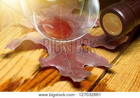 Red wine spilled from a glass on a wooden table on which the leaves and bottle