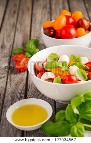 Italian Caprese salad with cherry tomatoes, small mozzarella and fresh basil, selective focus, copy space