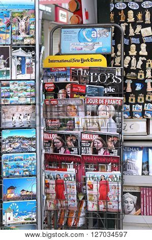 ATHENS GREECE - MAY 02 2015; Newsstand with international magazine publications souvenirs and postcards in Athens Greece - May 02 2015: Outdoor stand with postcards and souvenirs sold at city street