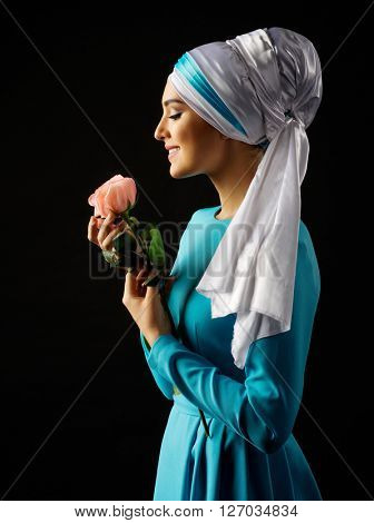 Muslim woman in blue dress with rose on black