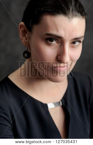 Sceptical brunette woman in black closeup portrait