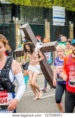 London United Kingdom - April 24 2016: London Marathon 2016. Runners in great costumes. Barefoot runner as Jesus with a cross on his back