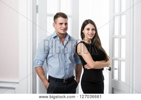 Well built muscular man in a shirt and beautiful girl in bussiness dress