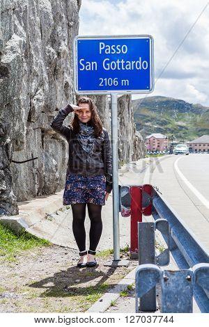 Girl standing under the Passo San Gottardo sign in the Gotthard region in Switzerland