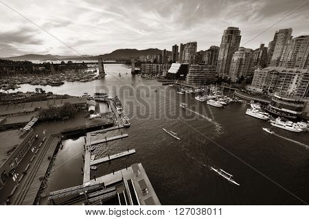 Vancouver harbor view with urban apartment buildings and bay boat in Canada.