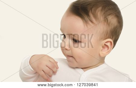 Cute baby boy looking to the side. Adorable baby portrait waving the hand not wanting something. Isolated on white.