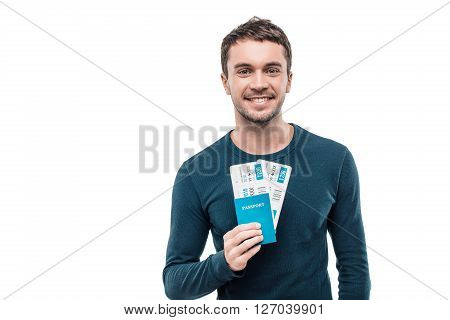 Portrait of stylish handsome young man isolated on white background. Man smiling, looking at camera and holding tickets with passport