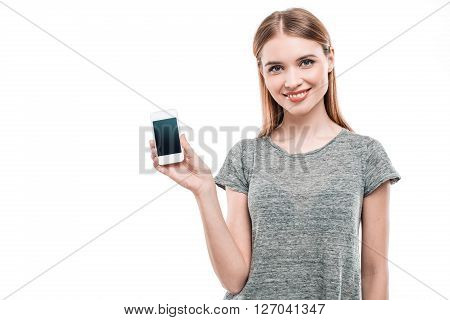 Portrait of stylish beautiful young woman isolated on white background. Woman smiling, looking at camera and showing mobile phone. Free space for logo