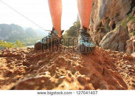 one rock climber legs on sunrise rock