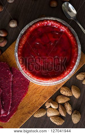 overhead view on fresh strawberry pie with nuts on side and frozen berries. Strawberry cake on dark table. Dark and moody style. Magic moon and mistic light