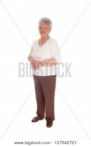 A senior citizen woman standing full length in brown pants and sweater isolated for white background.