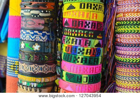 Numerous colorful wristbands with Oaxaca sight for sale at craft market